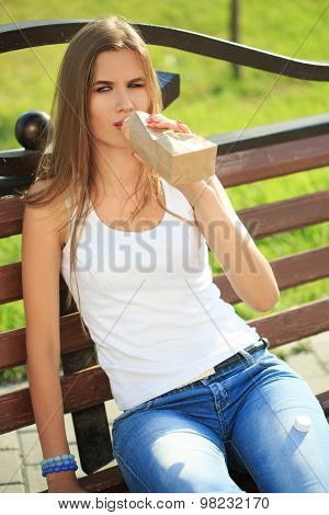 girl drinks from a bottle in a paper bag.
