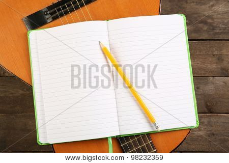 Music recording scene with guitar and memo pad on wooden table, closeup