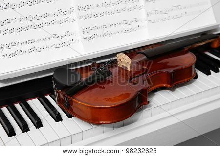 Piano with violin and music notes close up