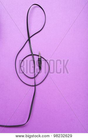Clef of headphones cable on purple background
