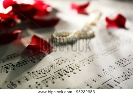 Beautiful rose petals with pearls on music sheets background