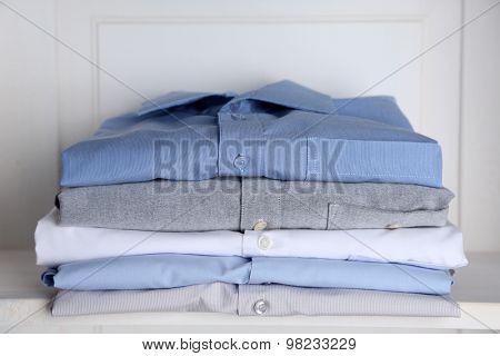 Business shirts on shelf in cupboard