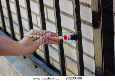 Hand With Brush Painting Metal Fence