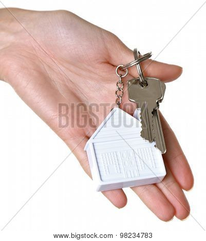 Female hand holding keys with house key chain isolated on white