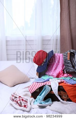 Suitcase with clothing on bed in room