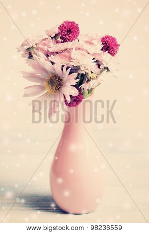 Beautiful flowers in vase on table on light background
