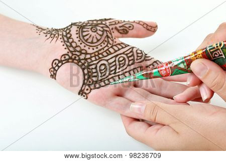 Image of henna applied on female hand isolated on white