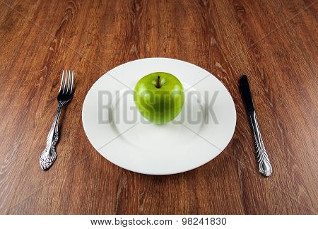Table Appointments And The Fresh Green Apple On A White Plate