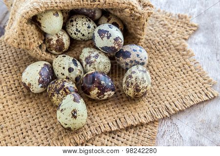 Quail Eggs In Burlap Sack On A Wooden Table