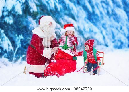 Kids And Santa Claus Opening Presents In Snowy Forest