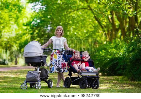 Woman With Kids In Stroller In A Park