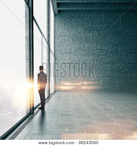 Businessman looking at sunrise in office