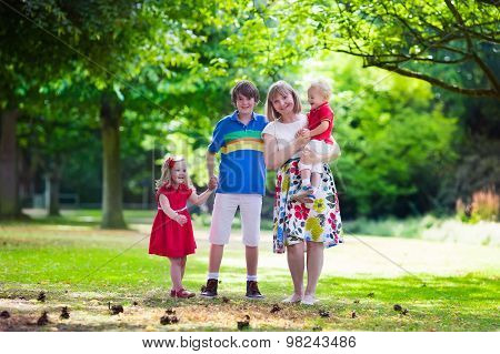 Grandmother And Children Walking In A Park