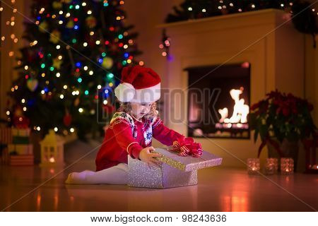 Kids Opening Christmas Presents At Fireplace