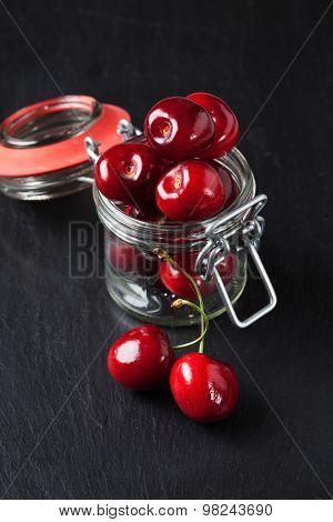 Sweet Cherries In Preserving Jar On Slate