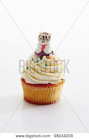 Close Up Of Vanilla Buttercream Cupcake With Cat Figurine Against White Background