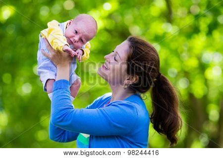 Mother Holding Newborn Baby In A Park
