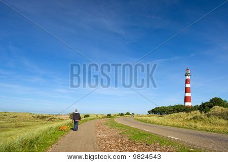 Man Is Walking In Landscape With Lighthouse