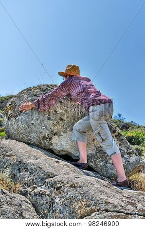 Woman moving the rock on the hill