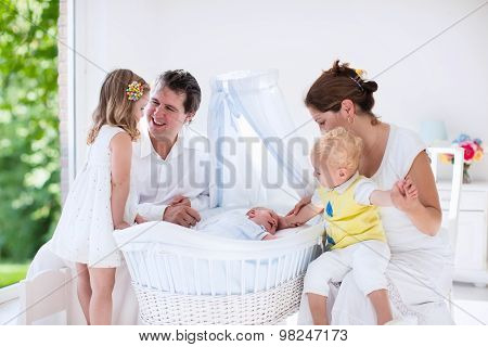 Family With Kids Playing With Newborn Baby