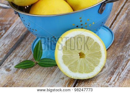 Half a lemon leaning against blue colander