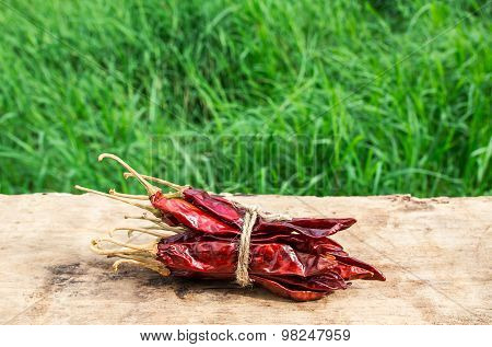 Dried Chili Peppers On Wooden With Green Grass Background