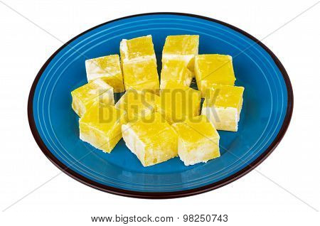 Yellow Turkish Delight In Blue Glass Plate Isolated On White