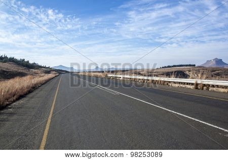 Straight Asphalt Road Lined With Dry Grass