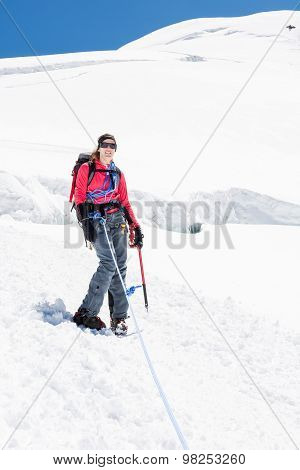 Female alpinist standing on glacier.