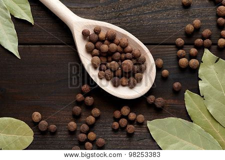 Allspice On A Wooden Spoon Surrounded By A Bay Leaf And Allspice