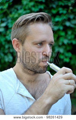 Man Smoking An Electronic Cigarette Outdoor