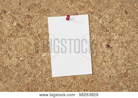 blank paper note pinned on a cork background