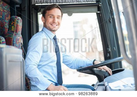Attractive young man is driving a public transport