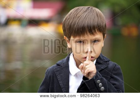 Young beautiful Little Boy has put forefinger to lips as sign of silence