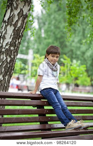 Stylish little boy sitting on a bench in a summer park