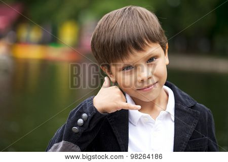 Little Boy making a call me gesture, against background of summer park