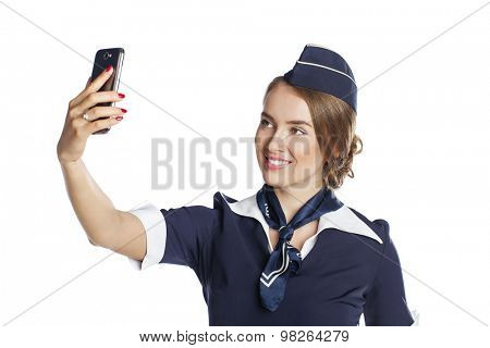 Beautiful young stewardess holding a smart phone isolated on white background