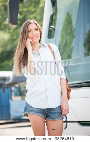 Attractive young woman is communicating near public transport