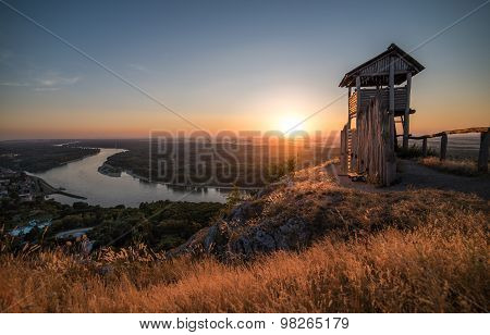 Wooden Tourist Observation Tower Above A Little City With River At Beautiful Sunset