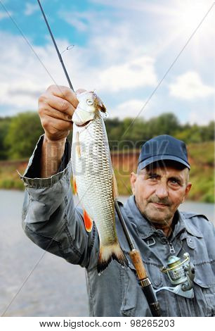 Chub In The Hand Of Fisherman Against The Sky And The River