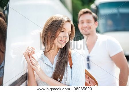 Attractive man and woman are flirting near a public transport