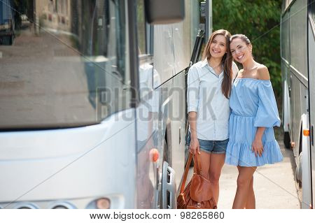 Attractive young female friends are traveling by public transport