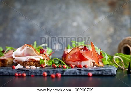 Sliced prosciutto with herbs and pomegranate seeds