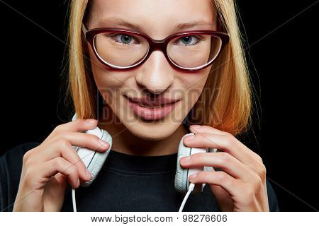 Cool young woman with headphones and nerd glasses