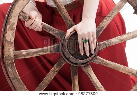 Vintage wooden wheel and woman's hands with a ring