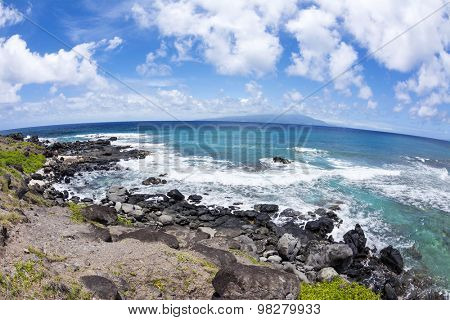 View of a tropical beach with a wide expanse of a rocky, boulder lined beach