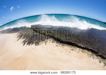 Close up of a reef on the shore of a tropical white sand beach with surf crashing into the reef