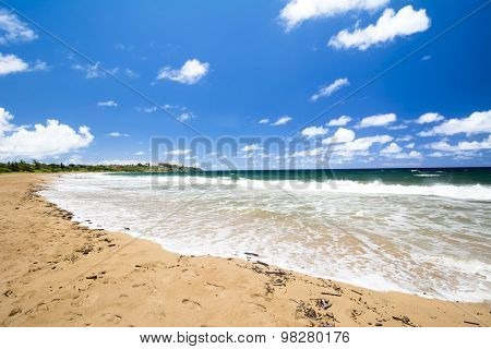 A beautiful white sand beach with clear blue water on a remote beach in Kauai Hawaii.