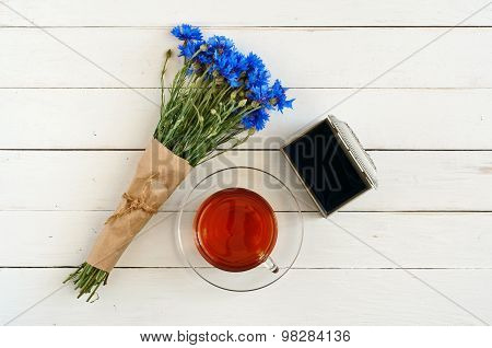 bouquet of flowers on white wooden background with a cup of tea with the old open box.