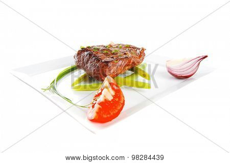 roast beef meat fillet entrecote served with tomato on white plate isolated over white background